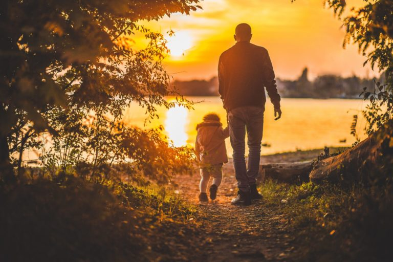 A man and his daughter walk towards the lake while the sun is setting.