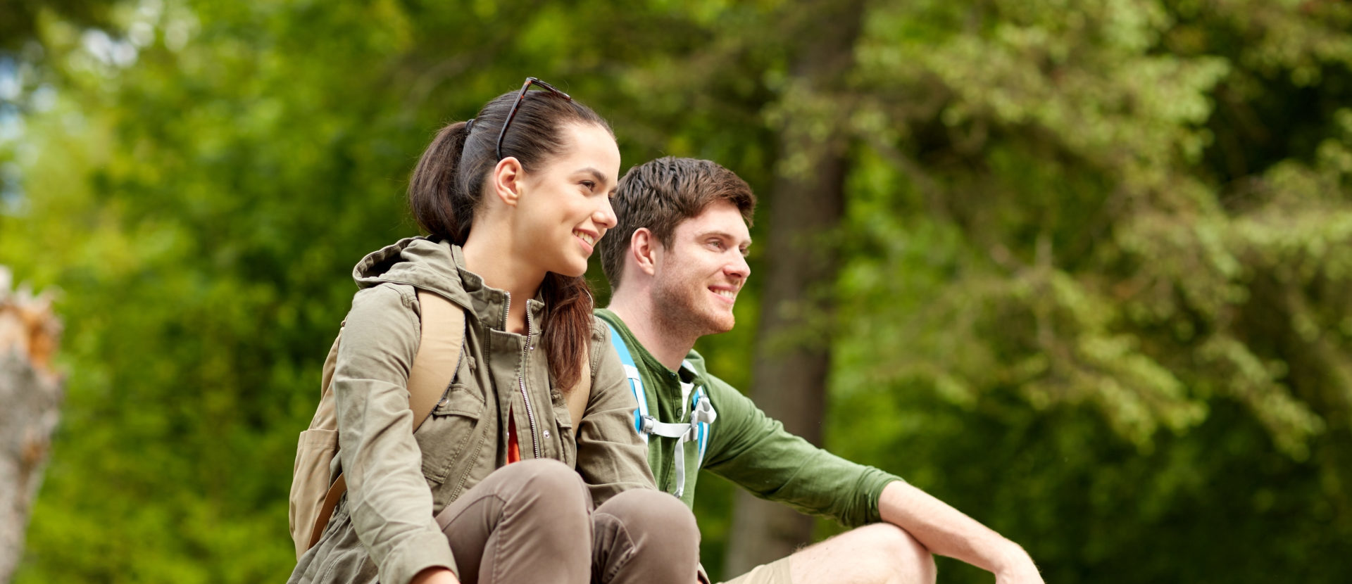 A young couple resting on a hike.
