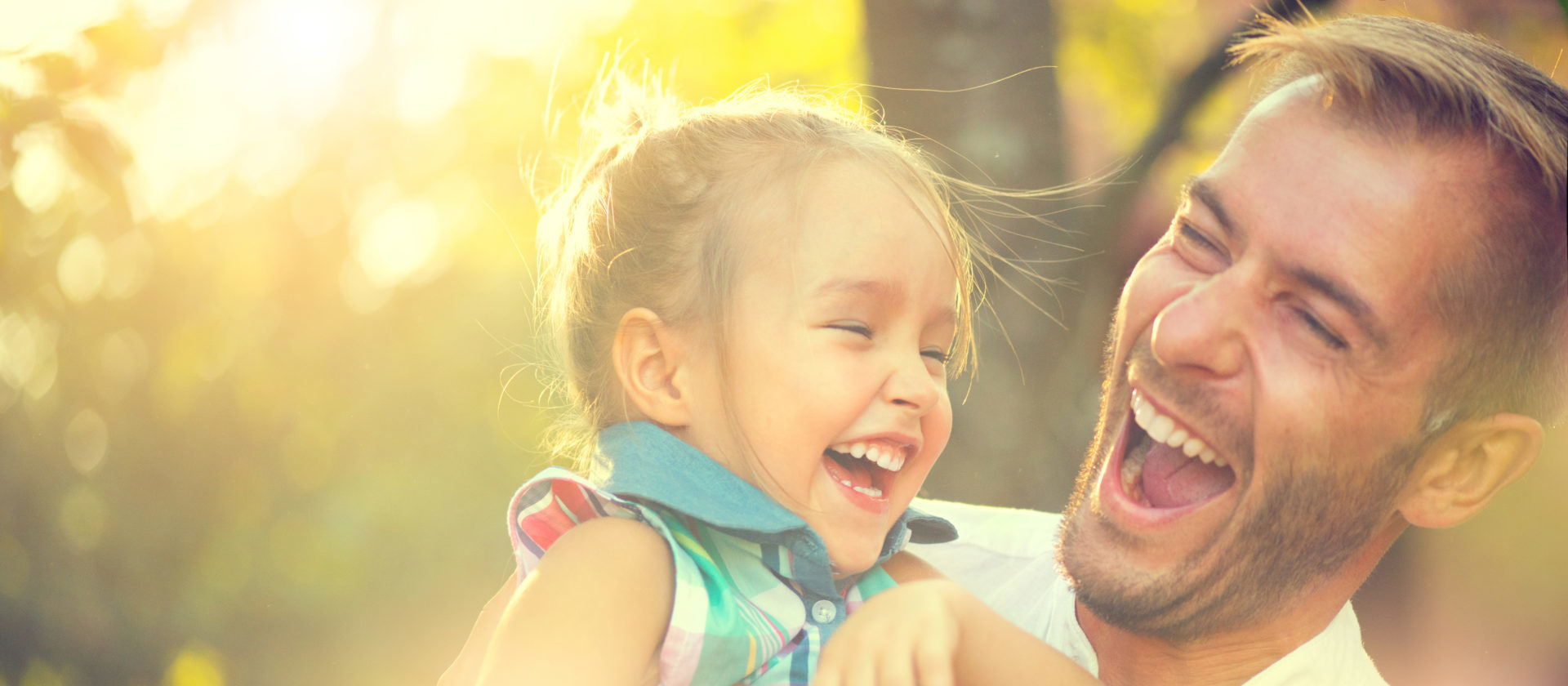 A man laughs with his daughter in this close up image.