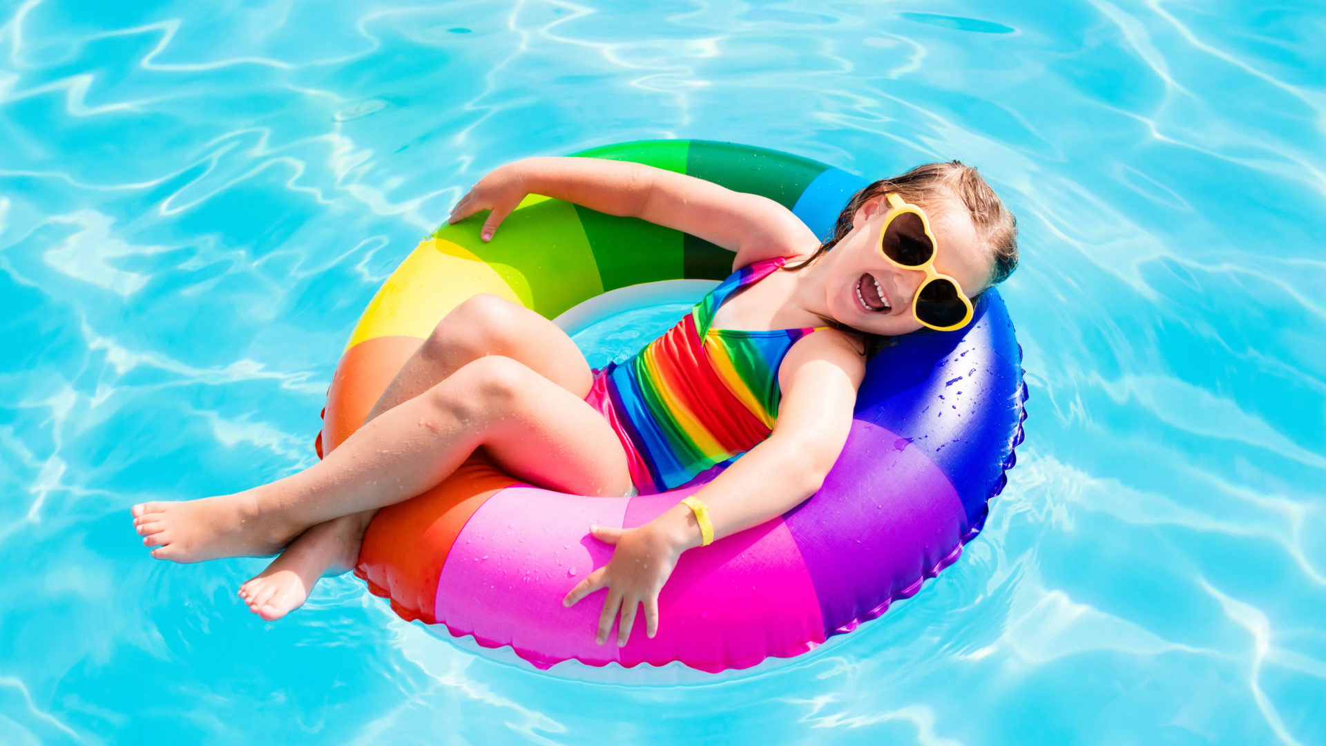 A young girl relaxes in the pool on a rainbow floaty.