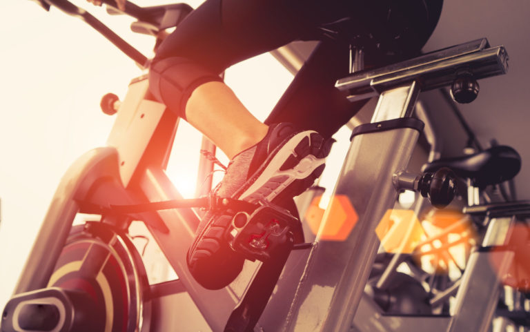 A bottom-up view of a woman riding an exercise bike.