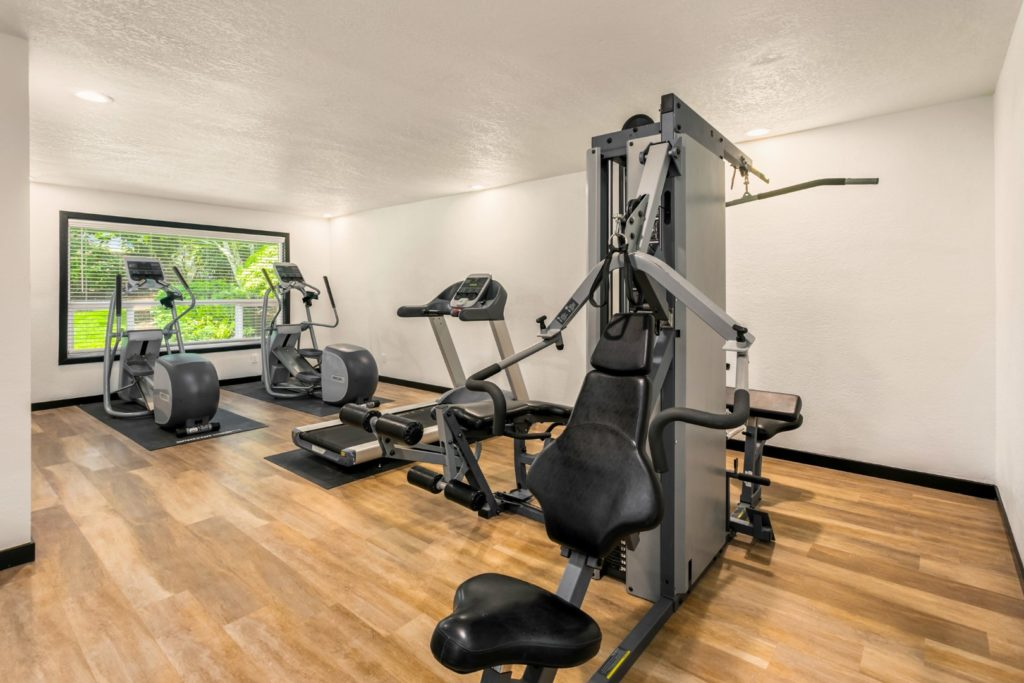 The exercise room has weight machines and treadmills.