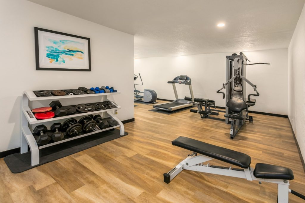 The exercise room features free weights and machines.